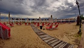 Deck chairs in a summer beach. A picture of deck chairs,and a small wooden pathway to a sea,in a summer beach,in a small town in Greece,Moudania Royalty Free Stock Photos