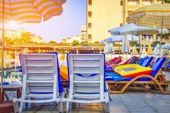 Deck chairs and sun loungers with umbrellas near swimming pool at resort tropical hotel in the morning. Summer vacation. Stock Photos