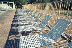 Deck chairs and swimming pool. With filter effect stock images