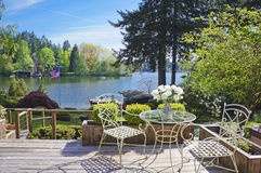 Deck with chairs and table with lake view. Deck with chairs and table with lake view and spring landscape Royalty Free Stock Photography