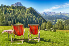 Deck chairs and table on the meadow Royalty Free Stock Images