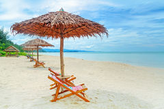 Deck chairs on tropical beach Stock Photos