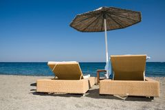 Deck chairs and umbrella on beach Stock Photography