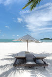 Deck chairs and umbrella on the beach Stock Image