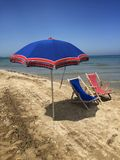 Deck chairs and umbrella on the beach Stock Photo
