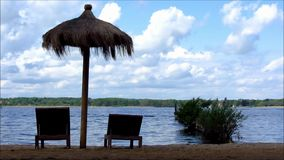 Deck chairs and umbrella at lake stock footage