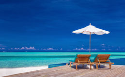 Deck chairs with umbrella overlooking infinity pool and lagoon stock image