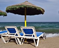 Deck chairs and umbrellas Stock Images