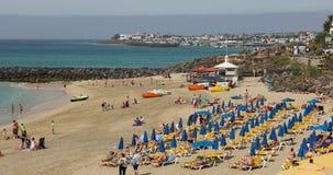 Deck chairs, umbrellas and bathers in Playa Dorada, Lanzarote, Canary Islands,. LANZAROTE, SPAIN - APRIL 19, 2018: deck chairs and umbrellas with tourist bathers stock video footage