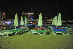 Deck chairs and umbrellas on the beach at night Royalty Free Stock Photography