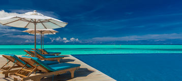 Deck chairs with umbrellas at Maldives resort with infinity pool Stock Photo