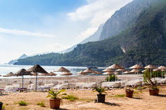 Deck chairs under thatched umbrellas on the beach of Çıralı. Stock Images