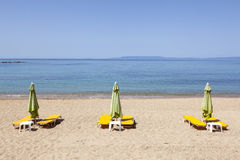 Deck chairs wait for people on Stoupa sandy beach in peloponnese Royalty Free Stock Images