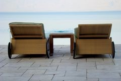 Deck Chairs by Water. A pair of woven deck chairs by the waters edge Royalty Free Stock Photo