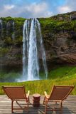 Deck chairs on the wooden floor for tourists. The warm July day in Iceland. Seljalandsfoss waterfall. Deck chairs on the wooden floor waiting for tourists stock photos