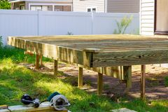 Deck construction work in garden with some torx circular saw. Overlooking backyard landscape stock photography