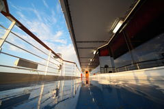 Deck of cruise ship in morning. Shining by light of rising sun. reflection in deck Stock Photos