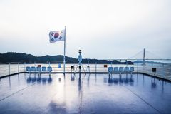 Deck on ferry from Jeju to Mokpo with South Korean flag with sun shining through and Mokpo bridge in background. On a sunny day royalty free stock photos