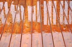 Deck floor in the rain. Wet, shiny hardwood deck floor during rain stock image
