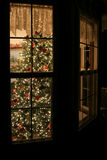 Deck the halls. View of exterior bay window with lighted Christmas tree inside Royalty Free Stock Images