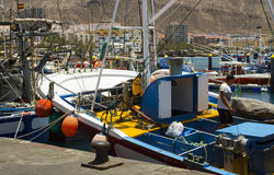A deck hand works on a local fishing trawler berthed in the crowded harbor in Los Cristianos in Spanish Island of Teneriffe Stock Images