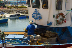 A deck hand works on a local fishing trawler berthed in the crowded harbor in Los Cristianos in Spanish Island of Teneriffe Royalty Free Stock Photo