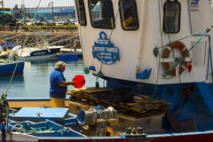 A deck hand works on a local fishing trawler berthed in the crowded harbor in Los Cristianos in Spanish Island of Teneriffe Stock Photo