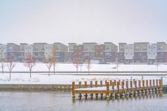 Deck on a lake overlooking buildings in Daybreak. Snowy wooden deck on a lake in Daybreak, Utah viewed in winter. Buildings against gloomy sky can be seen stock photo