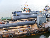The deck lay barge. Pipes and Lifting cranes on the ship. Equipment for laying a pipeline on the seabed Royalty Free Stock Photo