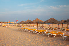Deck loungers in the beach at sunset. Paradise in Algarve, Portugal Stock Photo