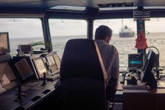 Deck navigation officer on the navigation bridge. He looks at radar screen. Watchkeeping, collision prevention at sea. COLREG stock photo
