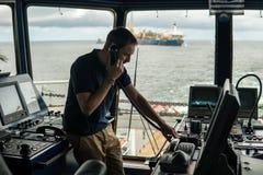 Deck navigation officer on the navigation bridge. He looks through binoculars. Deck navigation officer on the navigation bridge. He speaks by VHF radio, GMDSS Royalty Free Stock Photos