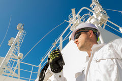Deck officer speaking by VHF on deck. Deck officer speaking by VHF on radar deck under blue sky Royalty Free Stock Image