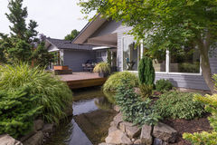 Deck over Water Landscaping. A water feature emulating a creek flows under a deck and between landscaped rocks with a contemporary home in the background Royalty Free Stock Photos