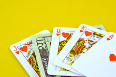 Deck of playing cards. And twenty dollars isolated on yellow background Royalty Free Stock Photo