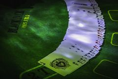 Deck of playing cards on the green table for Blackjack lighted with party lights stock images