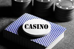 Deck of playing cards with a token on top with the word casino and casino chips royalty free stock image