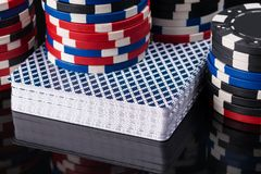 Deck of poker cards on a black background with poker. Chips Stock Photo
