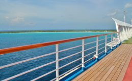Deck and rail on a cruise ship. Photo of a cruise ship deck and rail with the ocean in the background Stock Image