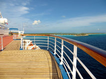 Deck and rail on a cruise ship. Photo of a cruise ship deck and rail with the ocean and an island in the background royalty free stock image