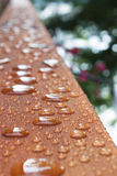 Deck rail after rain. Lengthwise view in selective focus, looking down cottage deck rail just after a summer rain. The water repels in little beads stock photos