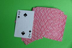 A deck of red cards with a peak deuce on a green table