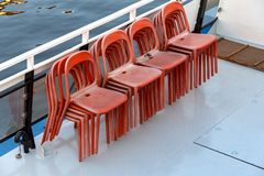 Deck of the ship and chairs. Plastic red chairs for passengers on the deck of a pleasure excursion boat stock image