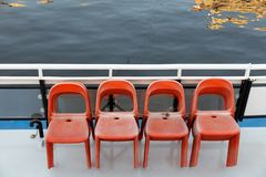 Deck of the ship and chairs. Plastic red chairs for passengers on the deck of a pleasure excursion boat royalty free stock image