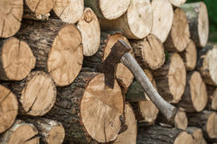 A deck of stacked logs and an axe Stock Image