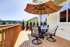 Deck with table, chairs and umbrella. Royalty Free Stock Images