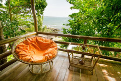 A deck with a view. Comfortable moon chair on deck with ocean view in background Royalty Free Stock Photo