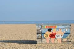 Deckchair在海滩与可笑的动画片在前边和海滩的聘用小屋在背景中 免版税库存图片