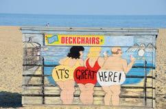 Deckchair在海滩的聘用小屋与可笑的动画片在前边 免版税库存照片
