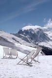 Deckchair στο χιόνι σε ένα χιονισμένο τοπίο βουνών στοκ εικόνες